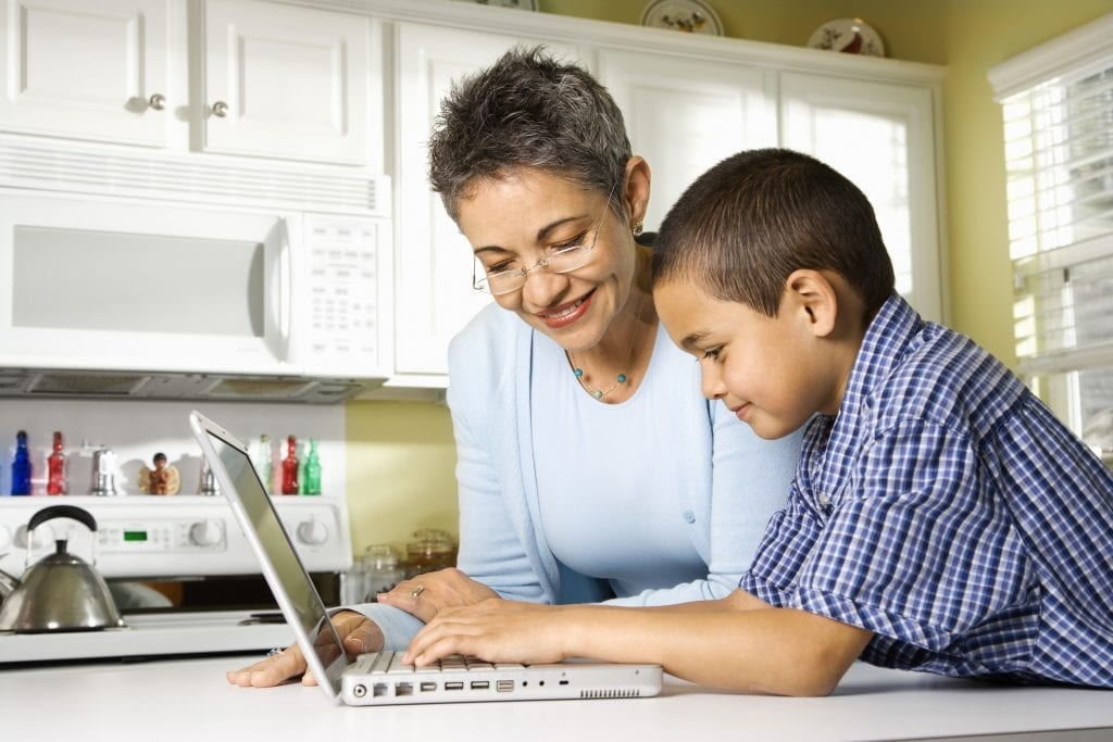 woman and young boy looking at computer.