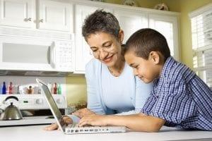 woman and young boy looking at computer.